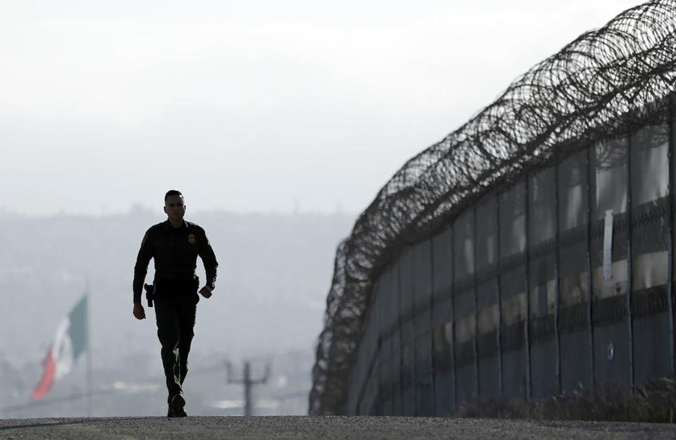 Border Patrol agent Eduardo Olmos walked near the secondary fence separating Tijuana, Mexico, background, and San Diego in San Diego.